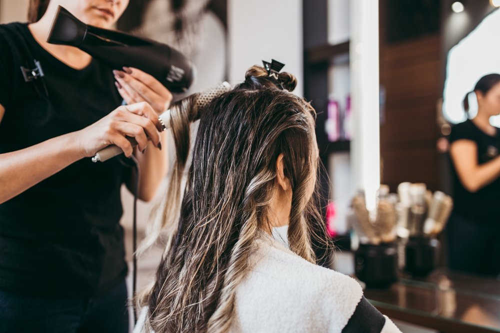 Hairstylist using styling tools on a client.