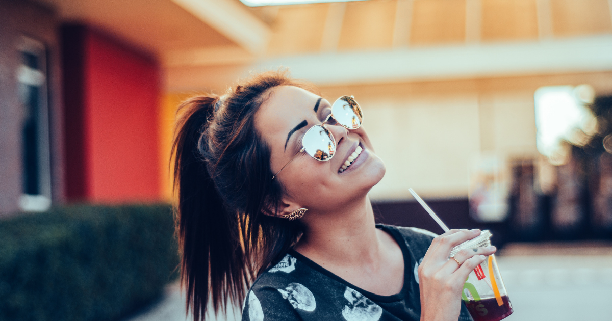 Smiling girl with sunglasses and a coffee.